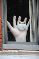 Disembodied Hand Supporting an Eyeball with a Brown or Hazel Iris